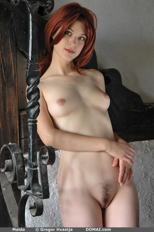 A nude redhead stands showing her breasts and pubic hair.