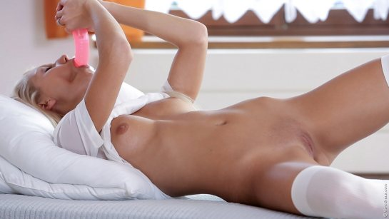 A nude blonde is lying in bed with her legs spread and sucking a dildo.
