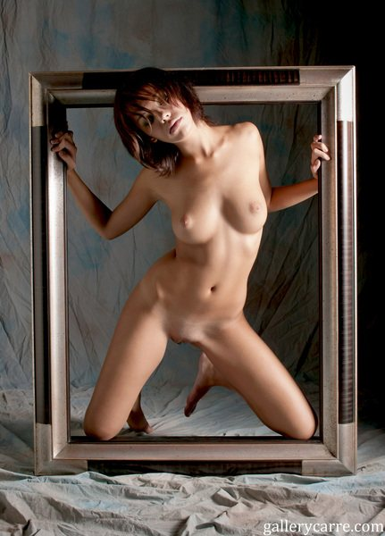 A nude girl is kneeling inside a large picture frame.