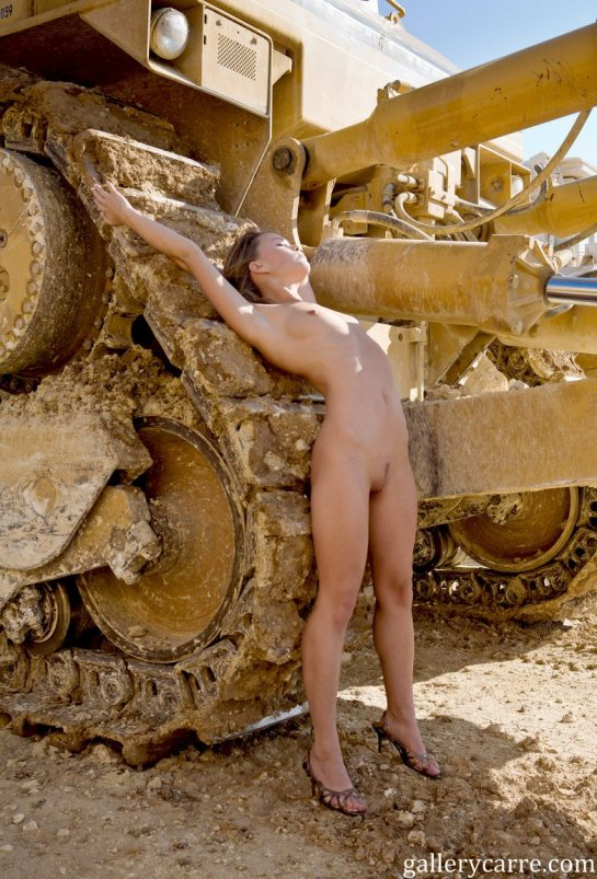 Mia is a totally nude blonde leaning against the tracks of a Caterpillar tractor.