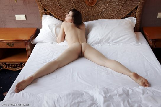 Oliviana is a pretty, totally nude, brunette lying on her stomach with her legs spread wide.