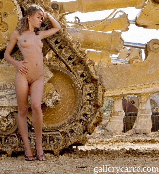 A pretty fully nude blonde is standing nest to a very large Caterpillar tractor.