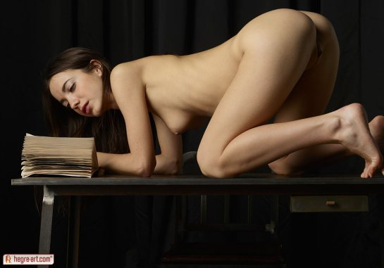 Kiki is a totally nude young brunette on her hands and knees on a table reading a book.