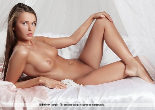 Pretty long haired brunette, Benita is lying totally nude resting on her elbow with her knee bent.