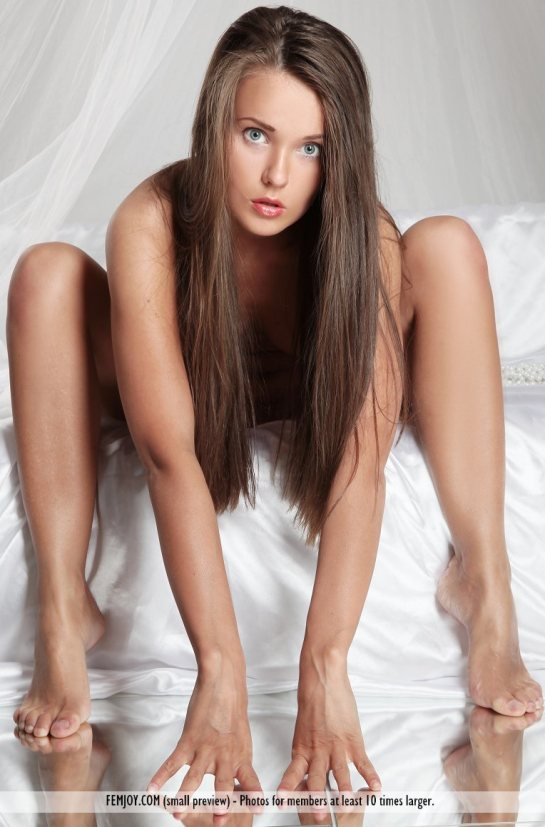 Beautiful long haired Benita is naked and leaning between herlegs.