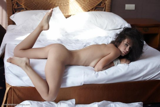 Karen is a nude brunette lying on her belly in bed with one leg in the air.