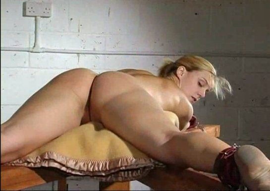 A nude blonde is lying on her belly with legs spread as her wrists and ankles are restrained by leather straps.