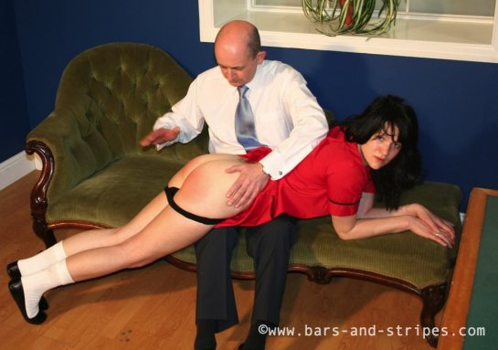 A young woman is lying across a man's lap with her panties pulled down as her raises his hand to spank her.
