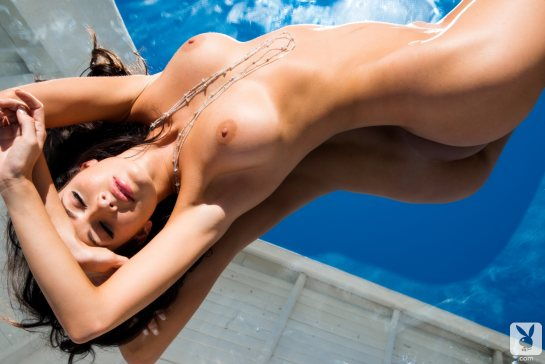 Gemma Lee Farrell Playboy Playmate November 2013 is stretching nude in a shallow pool.