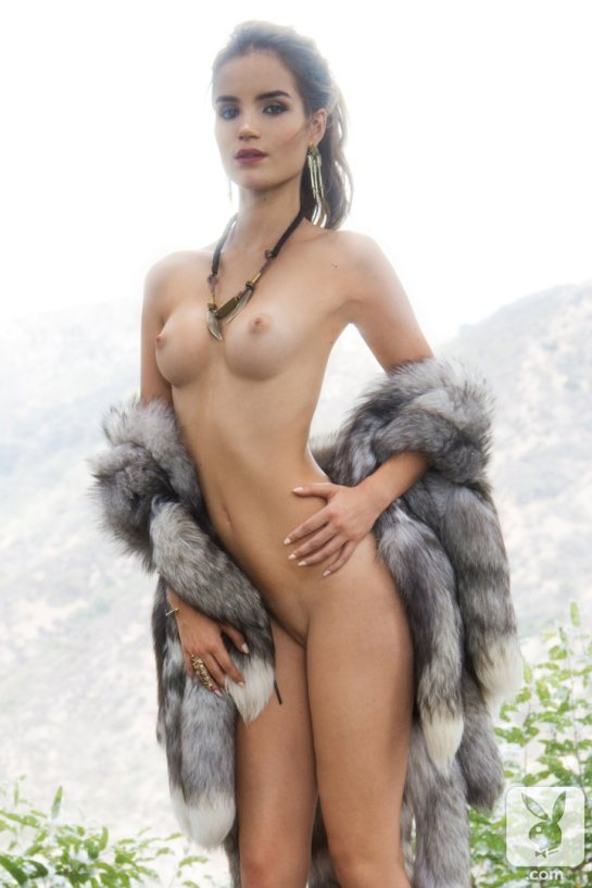 Roos Van Montfort January 2014 Playboy Playmate is standing nude holding a fur coat.