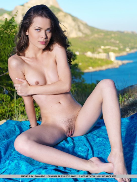 Blue eyed brunette beauty Amelie is totally naked spreading her legs.