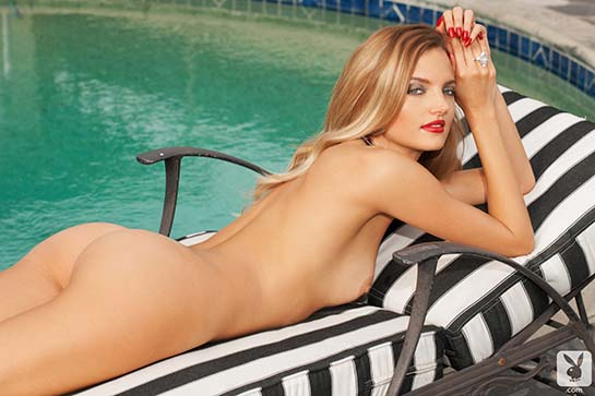 Amanda Booth Playmate Miss February 2014 is poolside lying naked on her belly.