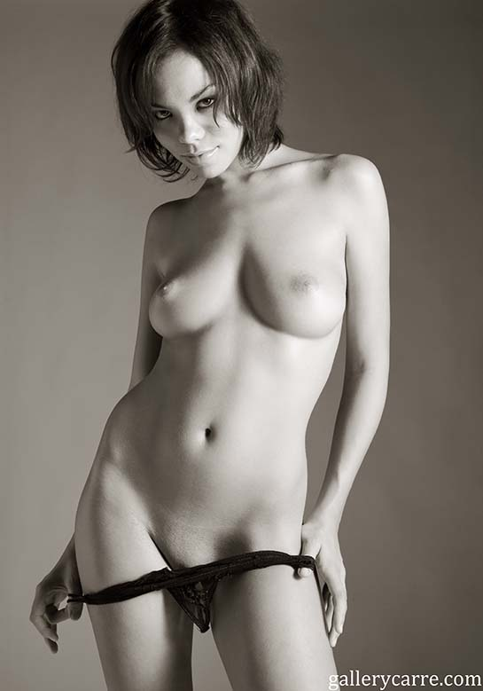 In this black and white photo pretty topless brunette Francois smiles as she pulls her panties down.