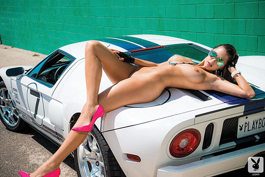Playboy Playmate Alyssa Arcè is lying totally nude across the trunk of a car.