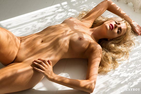 Blonde Stephanie Branton is  lying totally nude with an arm up.