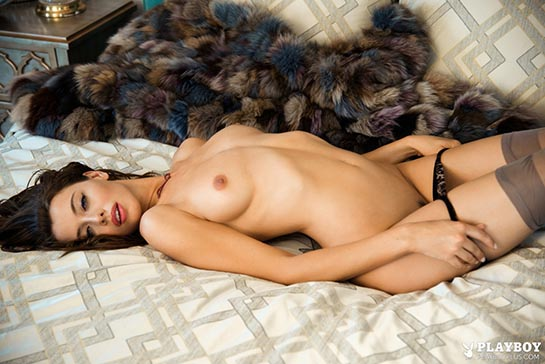 October 2014 PLAYBOY Playmate Roxanna June is a brunette lying naked showing her pubic hair.