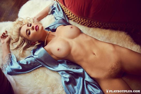 Kayslee Collins is lying naked, spreading her legs to show her bushy pussy.