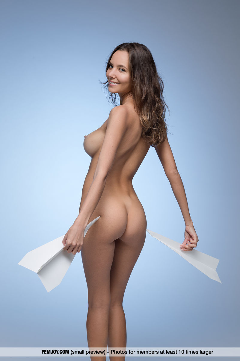 Nude Clover is seen from behind as she holds paper airplanes.