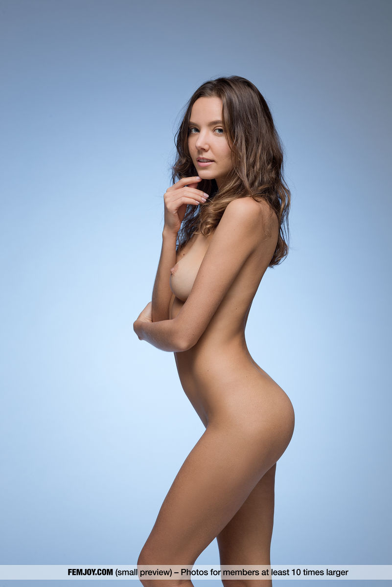 Pretty nude full breasted brunette Clover is standing sideways.