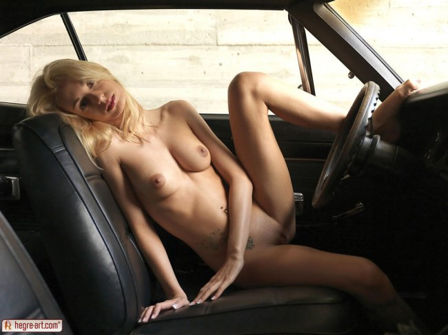 Nude blonde sitting in a car with her foot on the dashboard