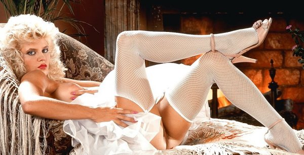 Ginger Lynn Allen is laying in bed topless and wearing white stockings and spiked shoes.