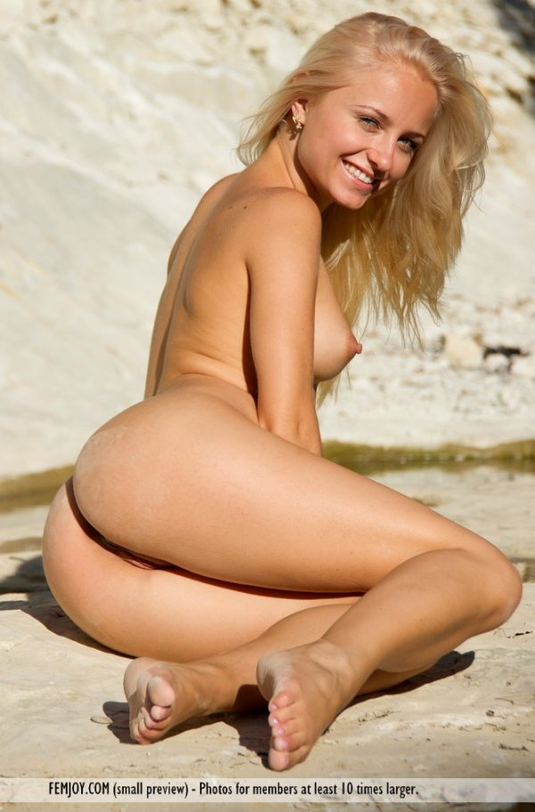 Hella, a totally nude blonde with thick nipples is sitting on the sand with her legs curled sideways.