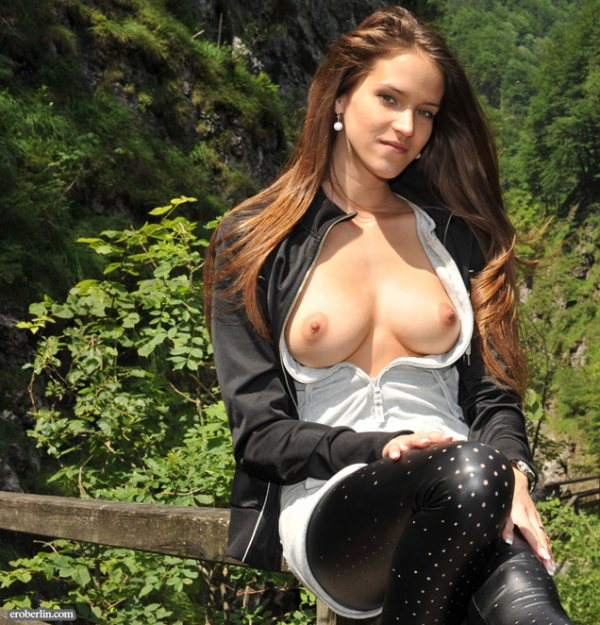 A pretty long auburn haired young woman's blouse is open and her breasts are showing.