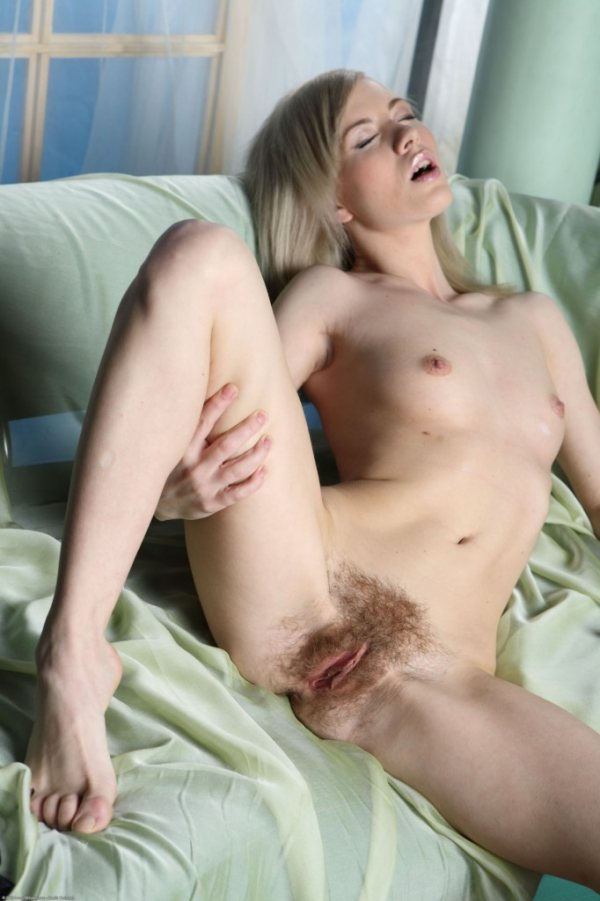 A nude blonde with very bushy blonde pubic hair spreads her legs.