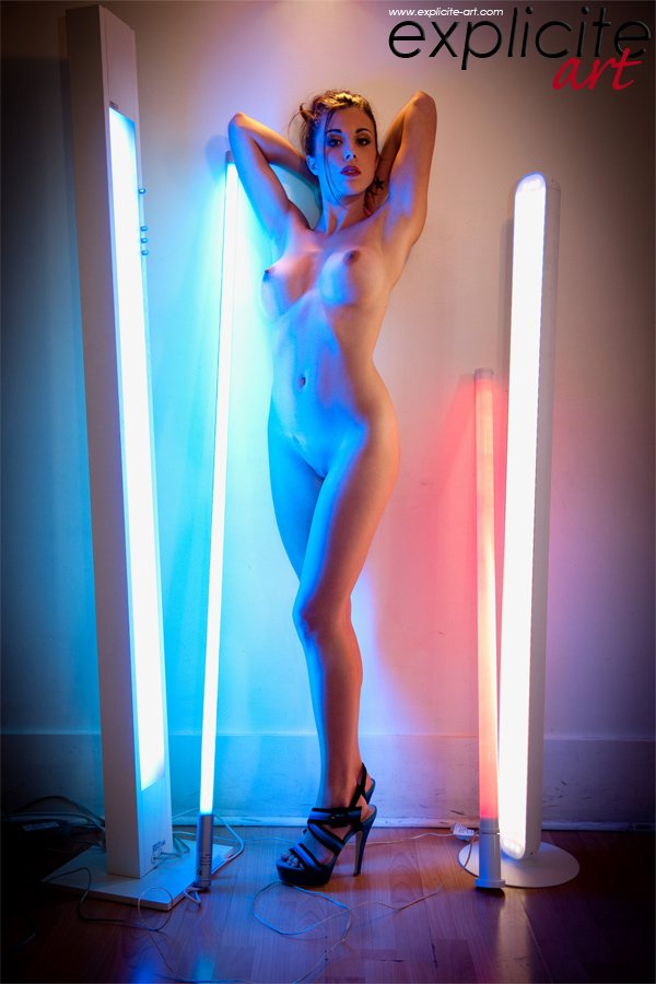 Big breasted Anouck is standing nude between florescent light tubes.