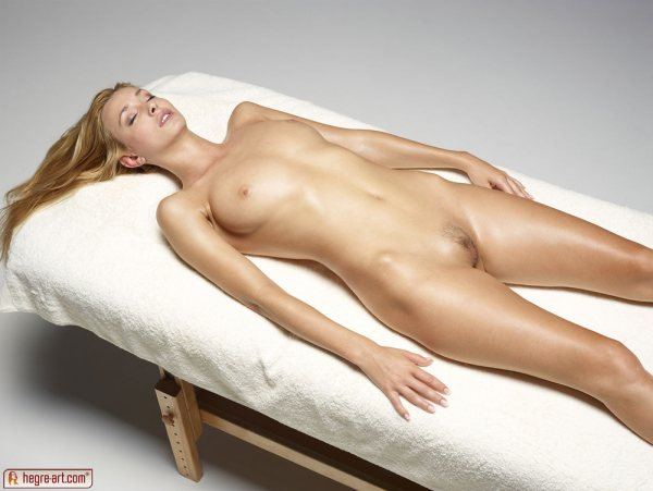 Coxy is a beautiful big breasted blonde with pubic hair lying on her back totally nude with her eyes closed.