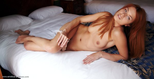 Kami is a beautiful redhead lying naked in bed.