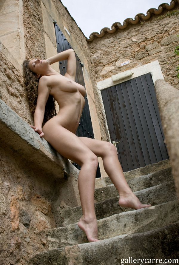 Full breasted nude Janine Mae is on an outdoor stone stairway leaning and stretching against the side of an old brick building.