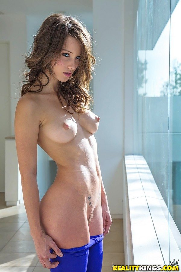 An auburn haired beauty is standing topless with her pubic hair exposed.