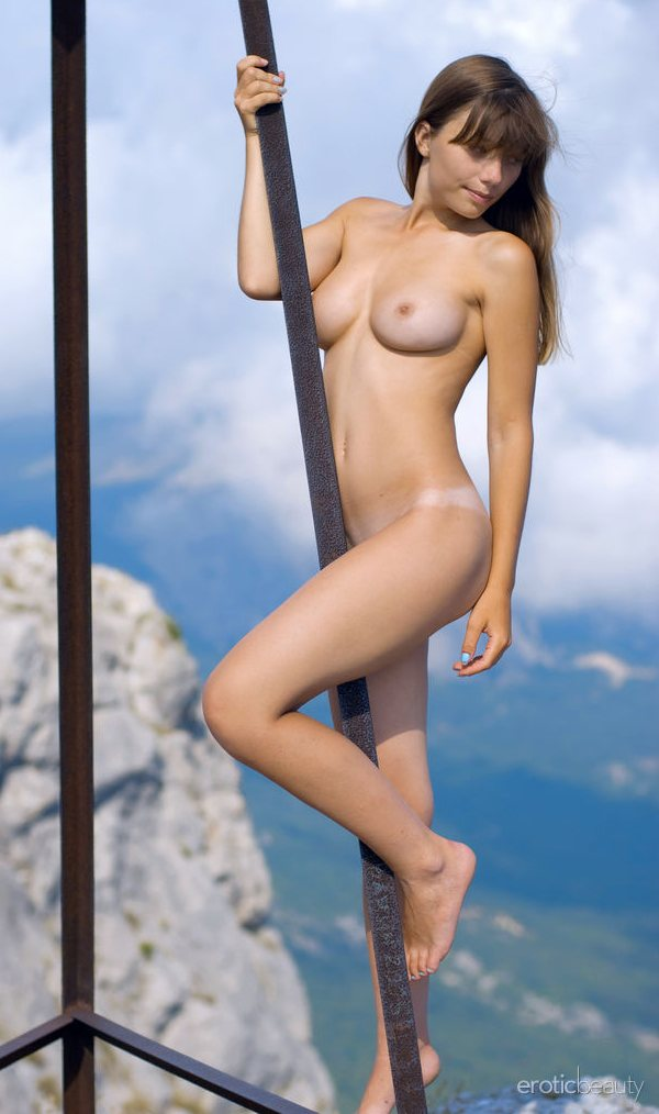 A totally nude model named Mine is standing on the metal girders of a tower on a mountain top.