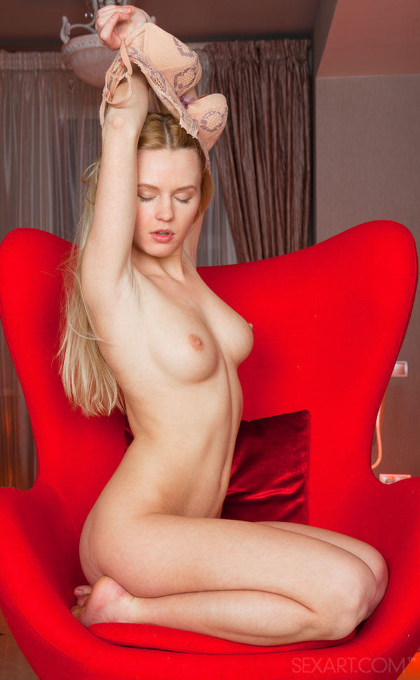Pretty blonde Xena is kneeling in a chair as she stretches her arms to pull her bra off.