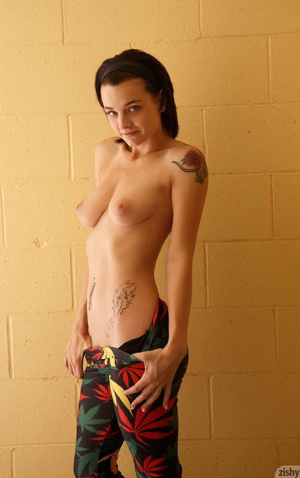 Kai Marley is standing topless showing her pretty breasts as she tugs her pants down a little.