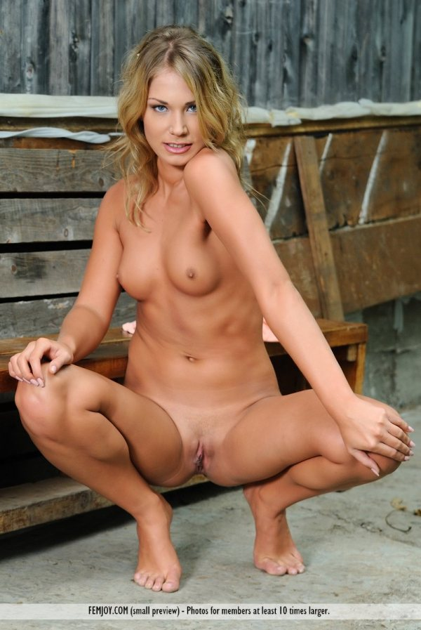 Pretty blonde nude Indolina is squatting with her legs spread wide.