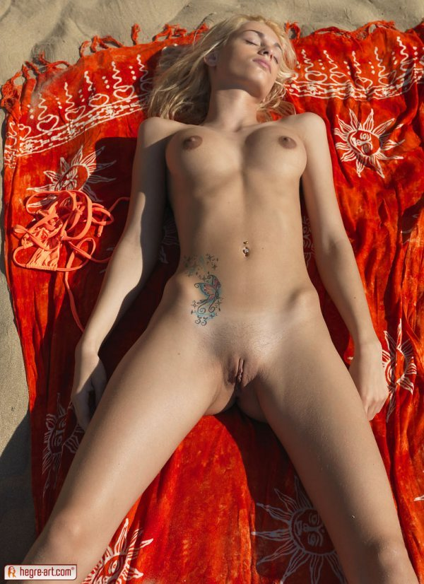 Erica is a fully nude blonde lying on her back on a beach blanket with her legs spread.