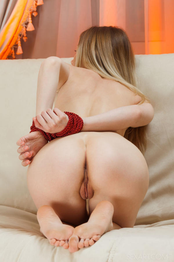 Nude blonde, Lenore, is in a dirty position on her knees showing her pussy crack while her wrists are tied behind her back.
